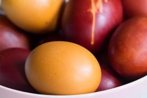 Gelbes mit Kurkuma gefärbtes Ei, hinten Zwiebelschalen